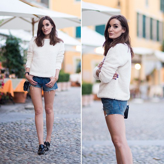 white sweater with crew neck with blue denim shorts and black ear burners