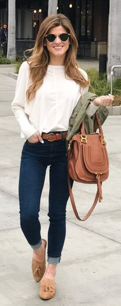 white long sleeve blouse with dark blue cuffed skinny jeans and tan loafers