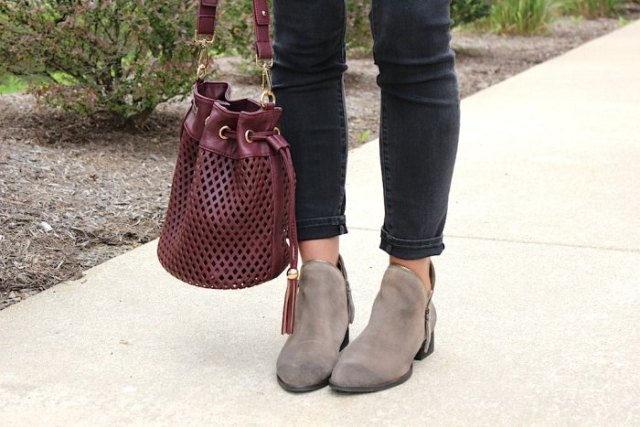 burgundy soft leather handbag with white blouse and black slim ankle jeans