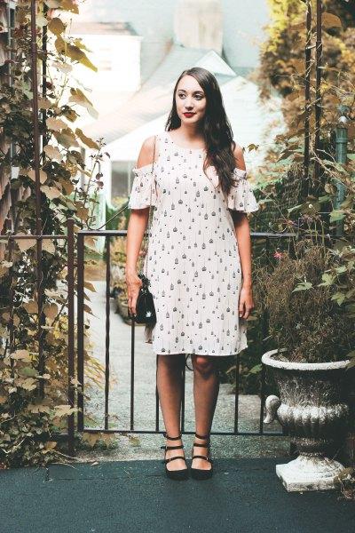 white cold shoulder print knee length dress with black shoulder leather handbag