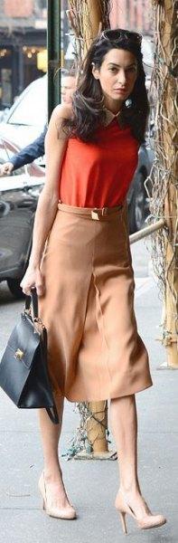 green sleeveless top with brown leather mini skirt and black handbag