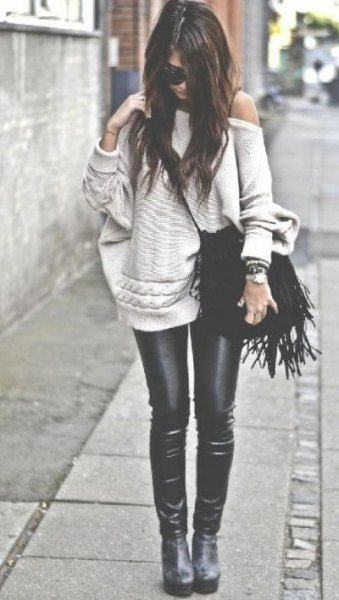 light pink sweater with a shoulder with black leather sticks