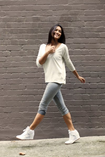 white bucket neck sweater with gray knee-length skinny jeans