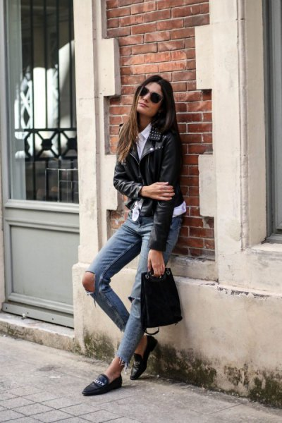 black moto jacket with gray heavily ripped jeans and leather case