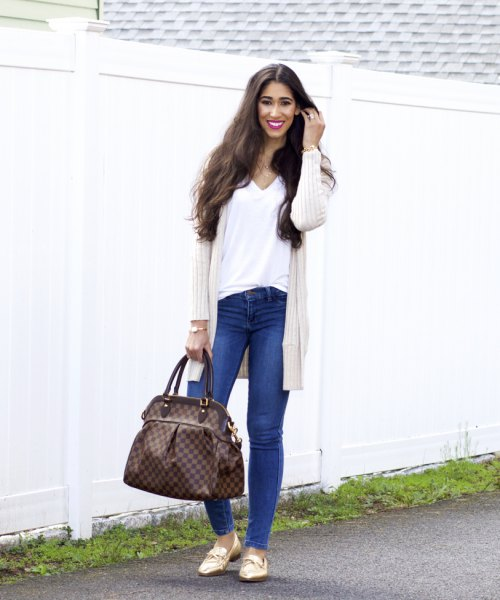 ivory cable knit longline cardigan with blue slim fit jeans and gold loafers