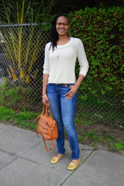white fitted sweater with blue skinny jeans and gold rounded toe burners