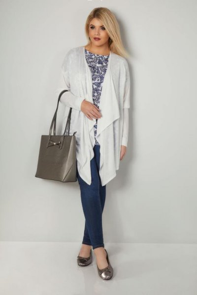 white longline cardigan with stem printed top and navy trousers