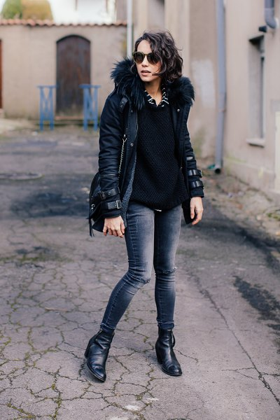 black short jacket with fur hood and dark gray skinny jeans