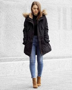 black cotton jacket with long fur in fur coat with slim ankle blue jeans