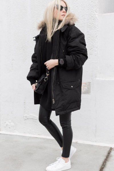 long oversized winter black jacket with dark gray skinny jeans and white sneakers