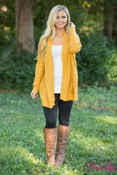 mustard yellow long-line sweater jacket with brown knee-high leather shoes