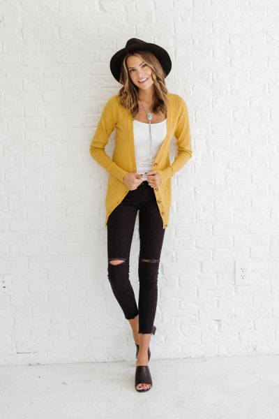 mustard yellow cardigan with black felt hat and ripped jeans