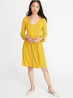 mustard yellow v-neck fit and flared knee-length dress with white flats
