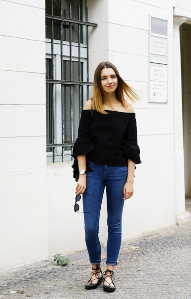 black of shoulder-warm blouse with blue skinny cuffed jeans