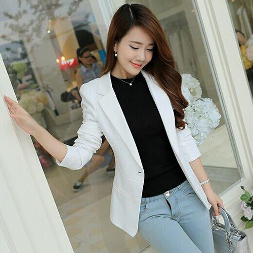 white blazer with black crew neck sweater and light blue jeans