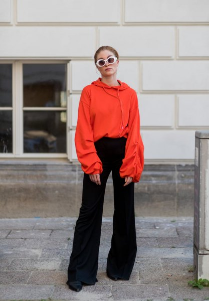 orange hoodie with black bell bottoms and boots