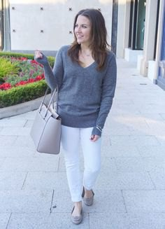 gray v-neck sweater with white slim fit jeans