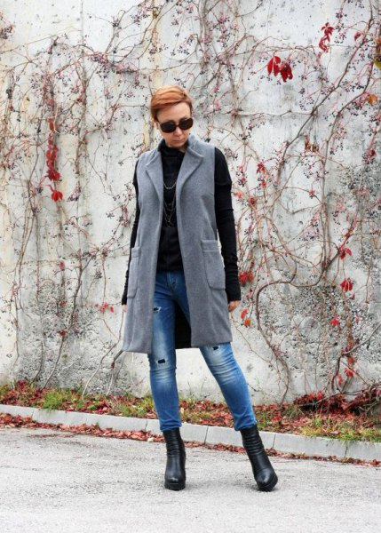 gray long-line wool vest with blue skinny jeans and black sweater