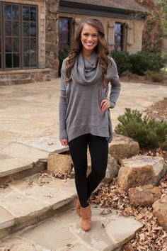 gray sweater with cabbage neck with black leggings and camel boots