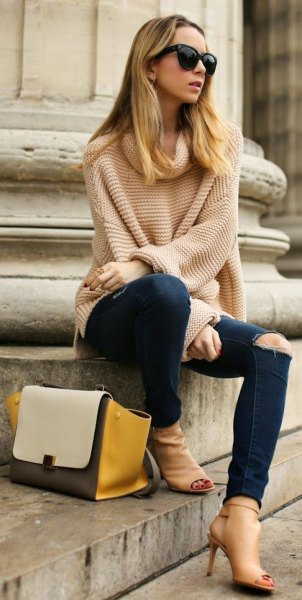 light pink large knit sweater with ripped dark jeans