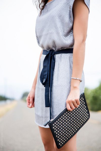 light blue belt sleeveless summer communication dress with black clutch bag