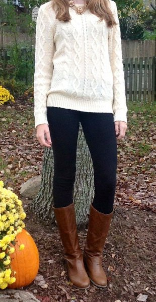 white knit sweater with black leggings and knee-high boots in brown leather