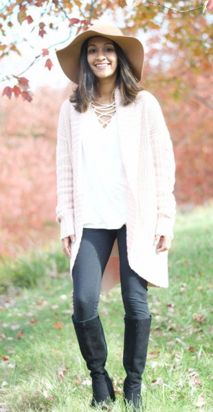 white knit cardigan with gray leggings and knee-high boots