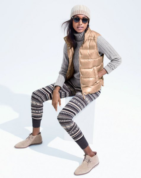 gold down vest with black and white tribal printed leggings