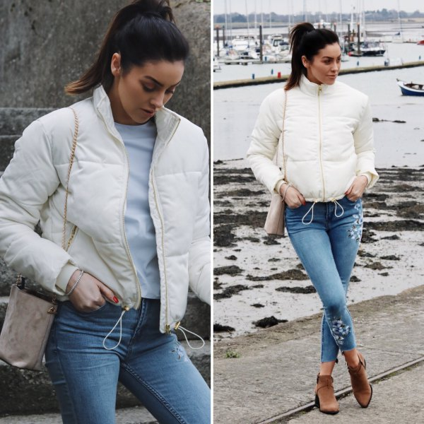 white down jacket with blue ripped cropped slim jeans