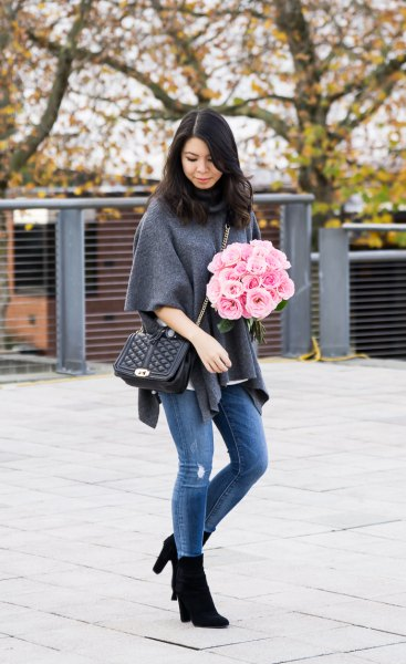 gray half-heated poncho shirt with blue jeans and black boots