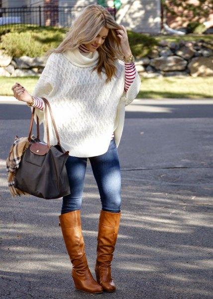 white knitted poncho shirt with blue skinny jeans and knee-high boots in brown leather