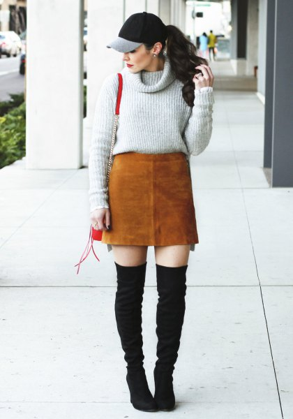gray sweater with cabbage neck with brown suede skirt and black thigh boots in the thigh