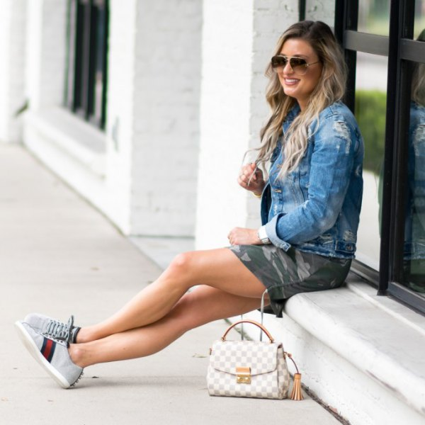 denim jacket with camo mini-shorts and light gray chambray sneakers