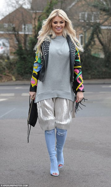 black printed studded leather jacket with silver shorts and light blue knee-high denim boots