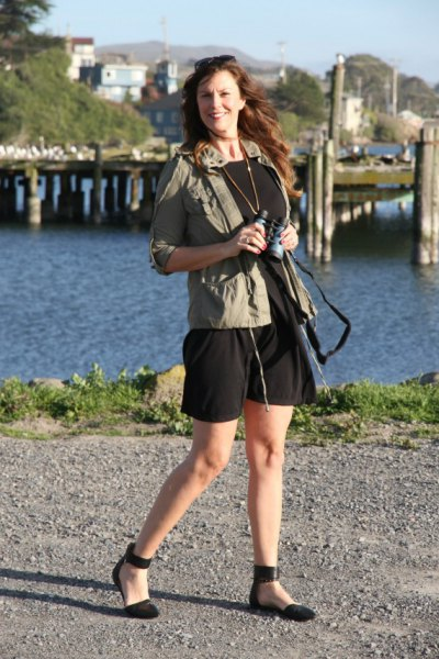 green windbreaker with black mini dress and ballet positions in the ankle