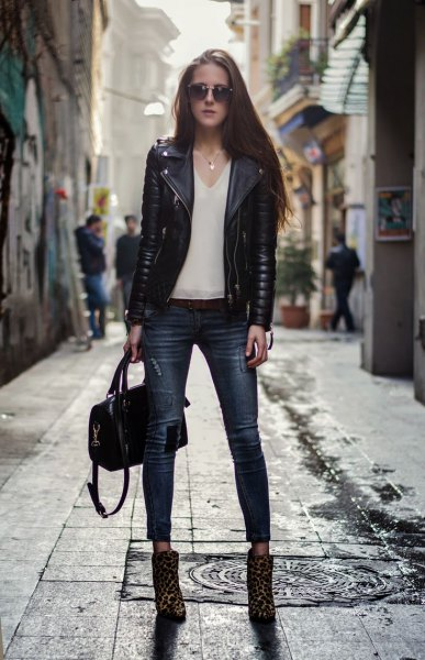 black moto jacket with white chiffon v-neck blouse and leopard print boots