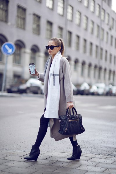 light gray long-line wool coat with white long scarf and black ankle boots