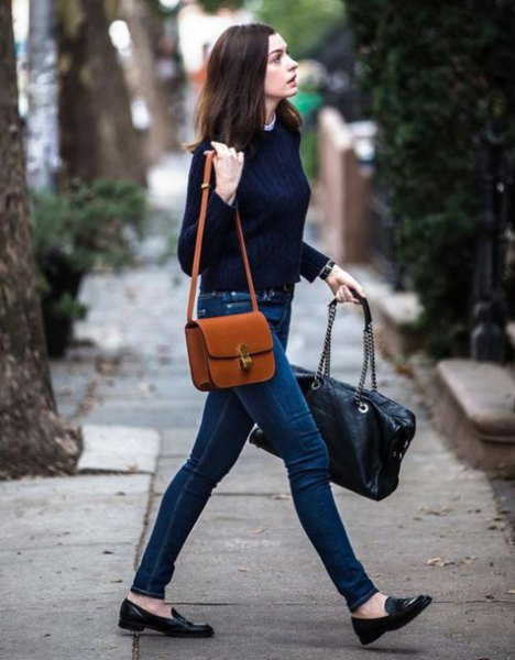 brown leather shoulder bag with black sweater and dark blue jeans