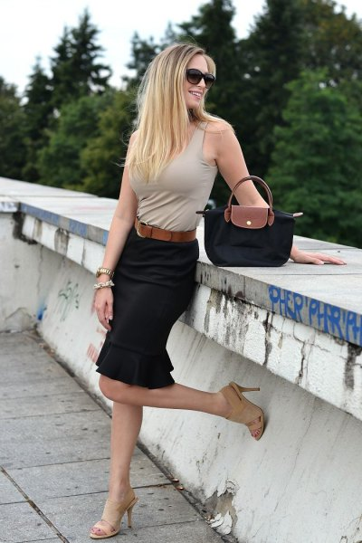 light pink sleeveless top with black pencil skirt and small purse