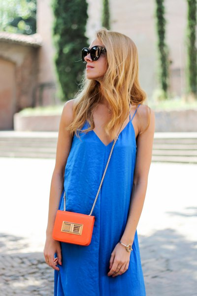 royal blue v-neck dress with orange mini handbag