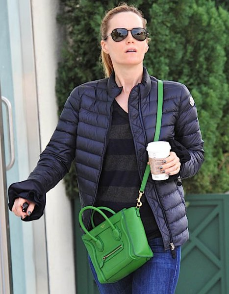 black down jacket with blue jeans and small handbag in brown leather