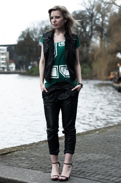 black vest with gray printed tee and leather pants