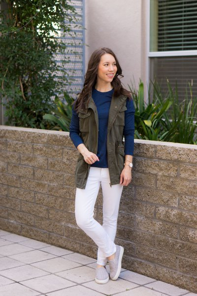 brown work vest with navy blue long sleeve top and white jeans