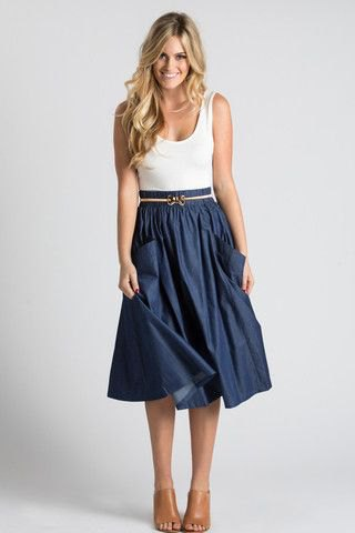 white scoop neck top with navy blue midi pleated belt skirt with pockets in front