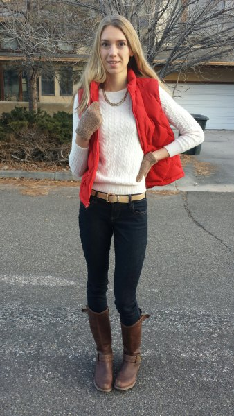 red vest with white cable knit sweater with black neck with black skinny jeans