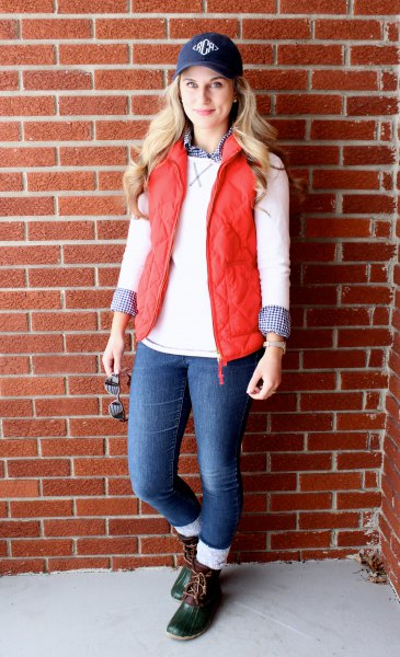 navy baseball cap with white sweater and quilted vest