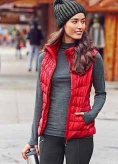 red nylon vest with gray knitted hat and gray sweater