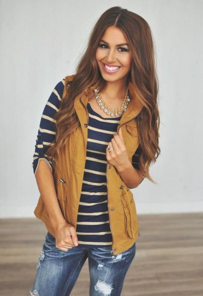 lime green hooded vest with navy and pink striped tee and ripped jeans