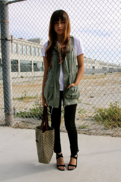 white tee with long military vest and black sandals