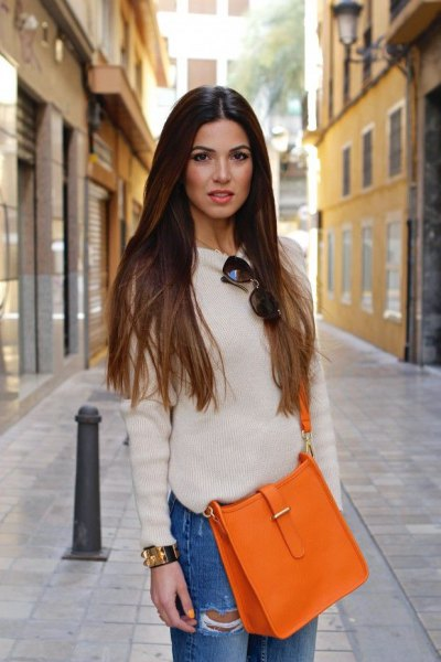 white fitted sweater with crew neck with blue boyfriends and orange handbag
